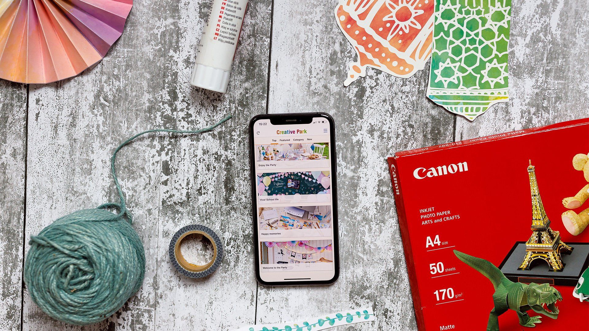 A smartphone displaying the Creative Park app surrounded by Canon printer paper, Creative Park designs and crafting tools.